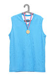 Sport jersey and a golden medal hanging on a hanger. Isolated on white background Stock Photos