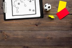 Sport judging concept. Soccer referee. Tactic plan for game, football ball, red and yellow cards, whistle on wooden Stock Photography