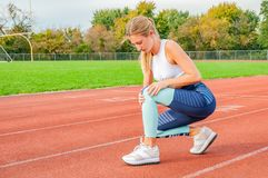 Sport knee injury. Woman has pain in knee after run outdoors stock images