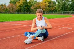 Sport knee injury. Woman has pain in knee after run outdoors stock image
