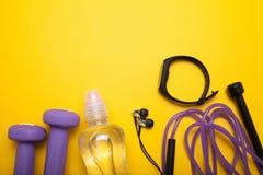 Sport kobieta protestuje na żółtym tle Dumbbells, butelka woda, hełmofony, skok arkana i sprawności fizycznej bransoletka, obrazy stock