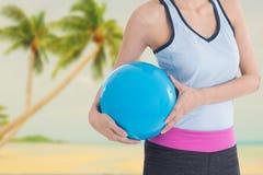 Sport kobieta trzyma plażową piłkę z plażowym obrazkiem w tle Zdjęcie Stock