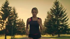 Sport kobiety bieg w parku przy zmierzchem Zmęczona biegacz przerwa dla przerwy przy parkową drogą zdjęcie wideo