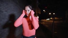 Sport kobiety bieg wzdłuż nocy miasta ulicy stawia dalej słuchawki zdjęcie wideo