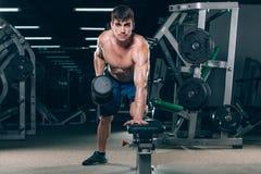 Sport, kondition, livsstil och folkbegrepp - böja muskler med hantlar i idrottshall royaltyfria bilder