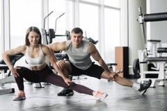 Sport, kondition, livsstil och folkbegrepp - le mannen och kvinnan som str?cker i idrottshall royaltyfri bild