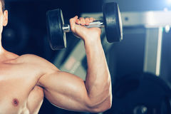 Sport, kondition, livsstil och folkbegrepp - muskulös kroppsbyggaregrabb som gör övningar med hantlar i idrottshall royaltyfri bild