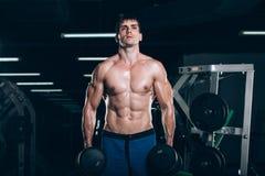 Sport, kondition, livsstil och folkbegrepp - muskulös kroppsbyggaregrabb som gör övningar med hantlar i idrottshall arkivfoto