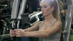 Sport, kondition, livsstil och folkbegrepp - som är nära upp av den unga kvinnan som böjer muskler på kabelidrottshallmaskinen arkivfilmer
