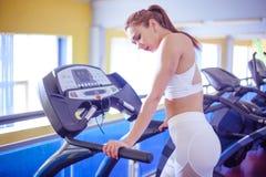Sport, kondition, livsstil, teknologi och folkbegrepp - spring för ung kvinna på trampkvarnen arkivfoton