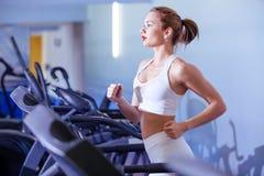 Sport, kondition, livsstil, teknologi och folkbegrepp - spring för ung kvinna på trampkvarnen arkivbild