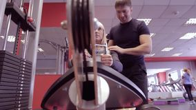 Sport, kondition, livsstil, tyngdlyftning och folkbegrepp - ung kvinna och personlig instruktör som böjer muskler i idrottshall stock video