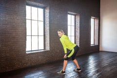 Sport konditionbegrepp Kvinna i sportswearen som poserar nära tegelstenwa royaltyfri bild