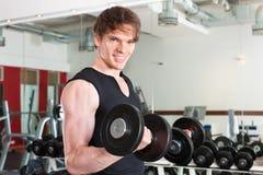 Sport - l'uomo sta esercitandosi con il barbell in ginnastica Immagine Stock