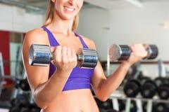 Sport - la donna sta esercitandosi con il barbell in ginnastica Fotografia Stock
