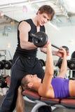Sport - le couple s'exerce avec le barbell en gymnastique Photographie stock