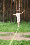 Sport, leisure, recreation and healthy active lifestyle concept. Man slacklining walking and balancing on a rope, slackline outdoors in forest Stock Photo