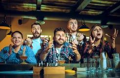 Sport, les gens, loisirs, amitié et concept de divertissement - passionés du football heureux ou amis masculins buvant de la bièr Image libre de droits