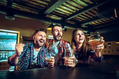 Sport, les gens, loisirs, amitié et concept de divertissement - passionés du football heureux ou amis masculins buvant de la bièr Photo libre de droits