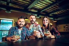 Sport, les gens, loisirs, amitié et concept de divertissement - passionés du football heureux ou amis masculins buvant de la bièr Image stock