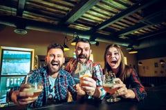 Sport, les gens, loisirs, amitié et concept de divertissement - passionés du football heureux ou amis masculins buvant de la bièr Images stock