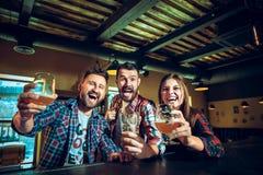 Sport, les gens, loisirs, amitié et concept de divertissement - passionés du football heureux ou amis masculins buvant de la bièr Images libres de droits