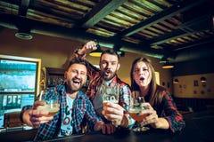 Sport, les gens, loisirs, amitié et concept de divertissement - passionés du football heureux ou amis masculins buvant de la bièr Photos libres de droits
