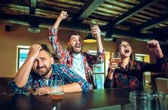 Sport, les gens, loisirs, amitié et concept de divertissement - passionés du football heureux ou amis masculins buvant de la bièr Photos stock