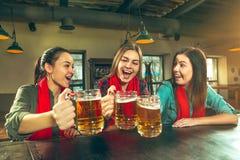 Sport, Leute, Freizeit, Freundschaft und Unterhaltungskonzept - glückliche Fußballfane oder Freundinnen, die Bier trinken und lizenzfreie stockbilder