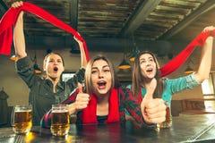 Sport, Leute, Freizeit, Freundschaft und Unterhaltungskonzept - glückliche Fußballfane oder Freundinnen, die Bier trinken und lizenzfreies stockbild