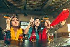 Sport, Leute, Freizeit, Freundschaft und Unterhaltungskonzept - glückliche Fußballfane oder Freundinnen, die Bier trinken und lizenzfreie stockfotografie