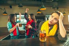 Sport, Leute, Freizeit, Freundschaft und Unterhaltungskonzept - glückliche Fußballfane oder Freundinnen, die Bier trinken und lizenzfreie stockfotos