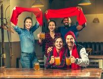 Sport, Leute, Freizeit, Freundschaft und Unterhaltungskonzept - glückliche Fußballfane oder männliche Freunde, die Bier trinken u lizenzfreie stockfotografie