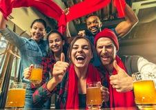 Sport, Leute, Freizeit, Freundschaft und Unterhaltungskonzept - glückliche Fußballfane oder männliche Freunde, die Bier trinken u stockfotos
