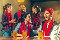 Sport, Leute, Freizeit, Freundschaft und Unterhaltungskonzept - glückliche Fußballfane oder männliche Freunde, die Bier trinken u lizenzfreies stockbild