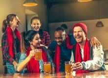 Sport, Leute, Freizeit, Freundschaft und Unterhaltungskonzept - glückliche Fußballfane oder männliche Freunde, die Bier trinken u stockbild