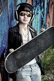 Sport life. Portrait of a trendy boy teenager with headphones and skateboard outdoors Royalty Free Stock Image