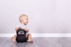 Sport is life. Happy laughing toddler sitting on the floor with kettlebell. Copy space.  Stock Photo