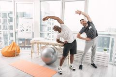 Pleasant nice men exercising. Sport is life. Pleasant nice men exercising while doing rehabilitation therapy royalty free stock photo