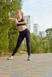 Sport and lifestyle concept - woman doing sports outdoors. She is a sport girl! Girl doing stretching exercises before Jogging Royalty Free Stock Photography
