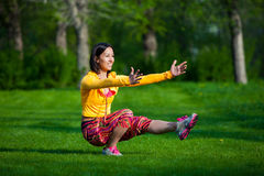 Sport and lifestyle concept - woman doing sports. Push ups or press ups exercise by young woman. Girl working out on grass crossfit strength training in the glow Stock Images