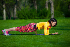 Sport and lifestyle concept - woman doing sports. Push ups or press ups exercise by young woman. Girl working out on grass crossfit strength training in the glow Royalty Free Stock Photo