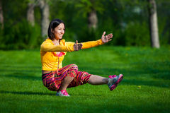 Sport and lifestyle concept - woman doing sports. Push ups or press ups exercise by young woman. Girl working out on grass crossfit strength training in the glow Stock Image