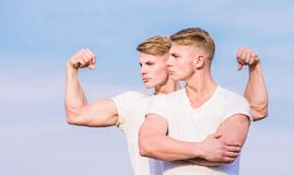 Sport lifestyle and healthy body. Attractive twins. Handsome strong twins. Men twins muscular brothers sky background. Men strong muscular athlete bodybuilder royalty free stock photography