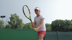 Sport lifestyle, professional athlete child girl plays at sports game and hitting racket on ball at professional red stock video