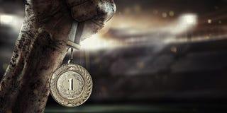 Sport, männliche Hand, die Goldmedaille hält Lizenzfreie Stockfotos