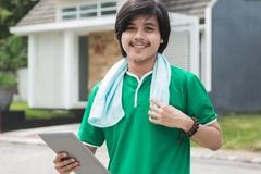 Sport male using tablet. Sport male exercising and using tablet pc outdoor Royalty Free Stock Image
