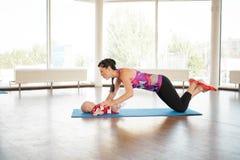 Sport mama stawia dziecka na dywaniku w gym fotografia stock