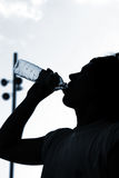 Sport man. A thirsty boy is drinking water after match. With copyspace Stock Images
