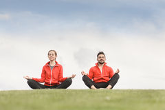 Sport Man And Woman Meditating In Park Stock Photos